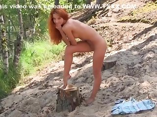 Redhead babe caresses herself in the forest